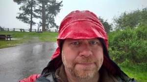 Dave enjoying the rain while breaking camp.