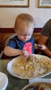 Alex enjoying Mama's biscuits and gravy so much he is using two spoon.