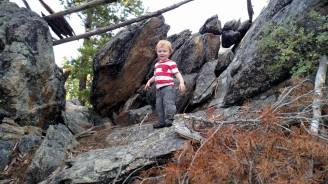 Alex climbing on a rock formation that was used as a shelter in the past.